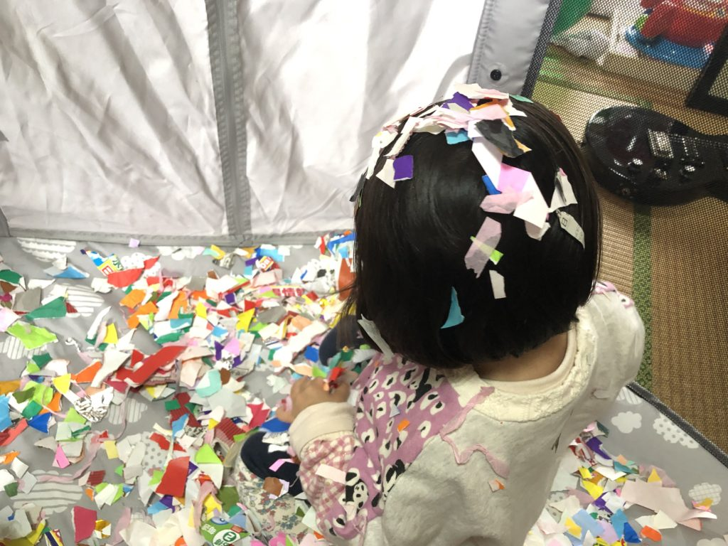 折り紙で遊ぶ花吹雪。ベビーサークル。
