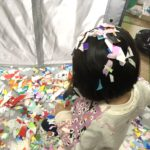 ベビーサークルで折り紙をちぎって遊ぶ娘。